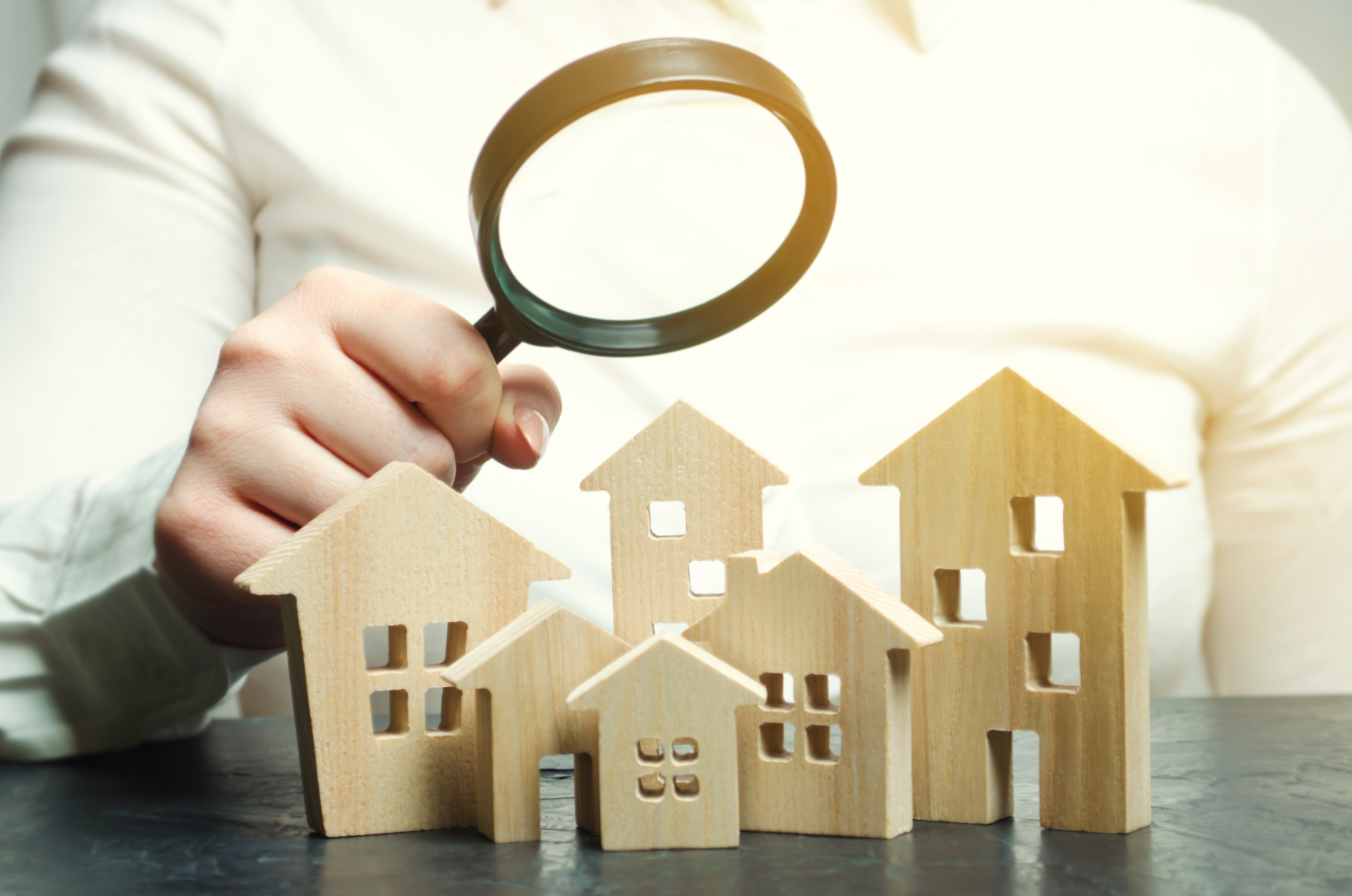 A woman is holding a magnifying glass over a wooden houses. Real estate appraiser. Find a house. Real estate market analysis
