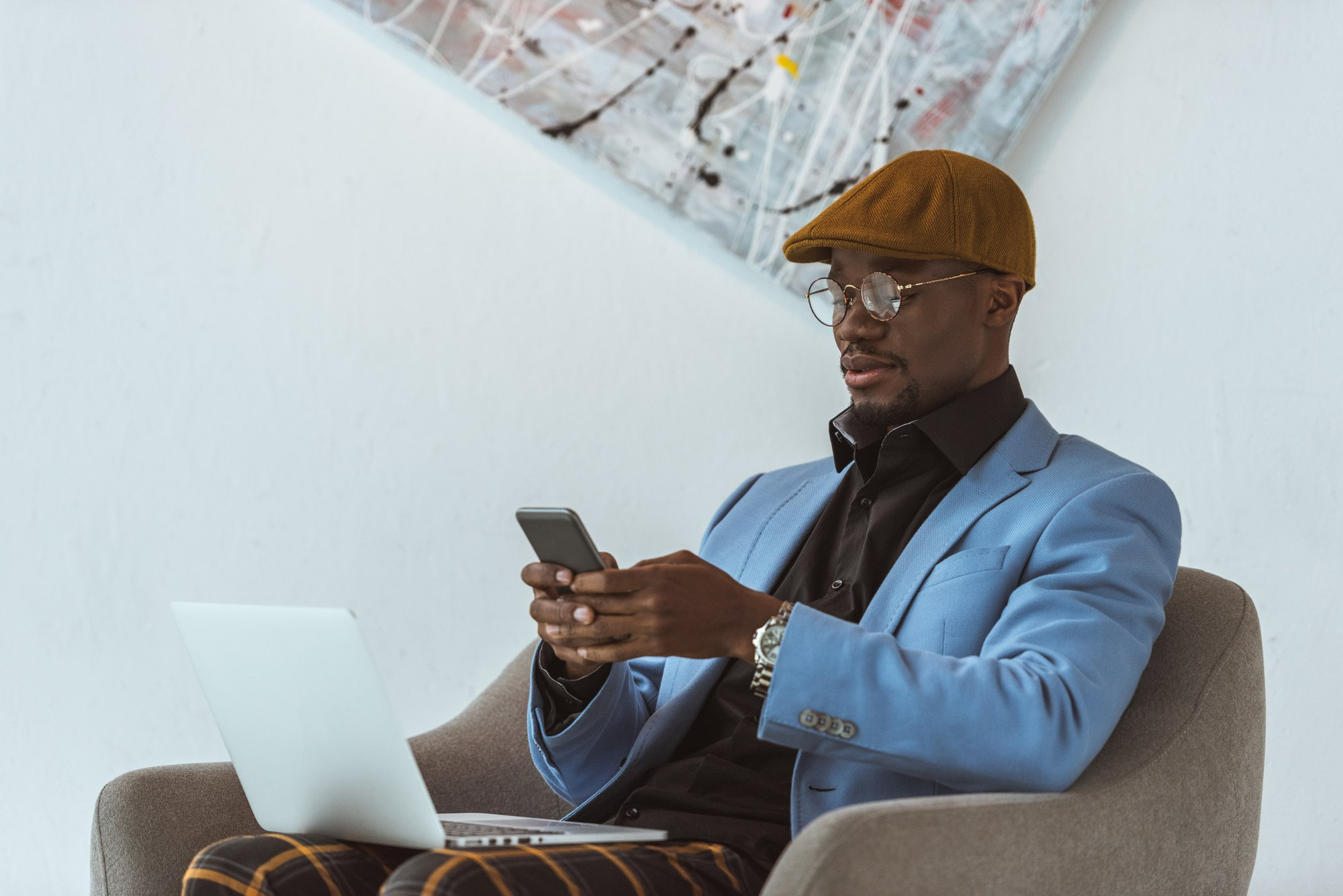 African american man using laptop and smartphone