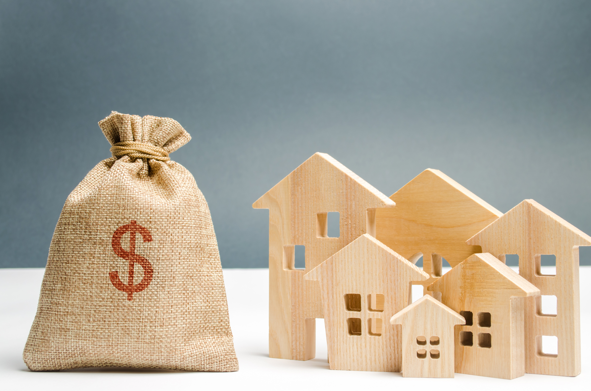Bag with money and dollar sign and wooden houses, Investing money in real estate. Saving and accumulation of money. Mortgage. Buying a home. Property sale. City budget