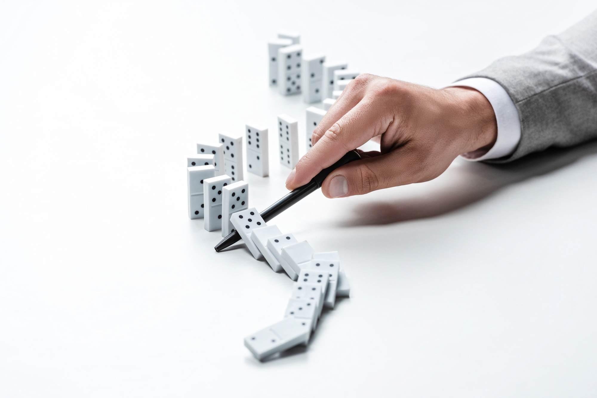 Cropped view of man preventing dominoes from falling with pen on white background