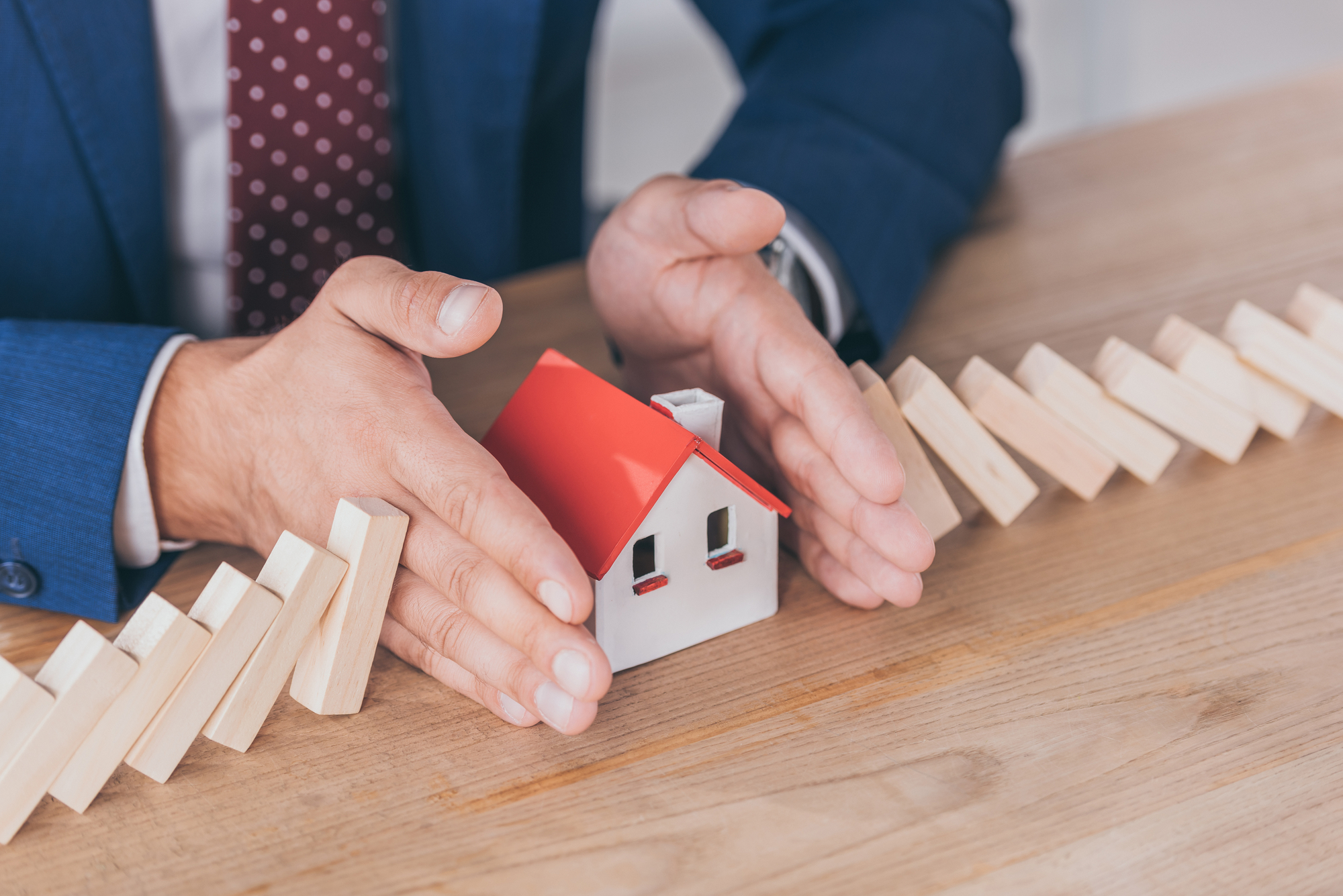 Cropped view of risk manager protecting house model from domino effect of falling wooden blocks with hands