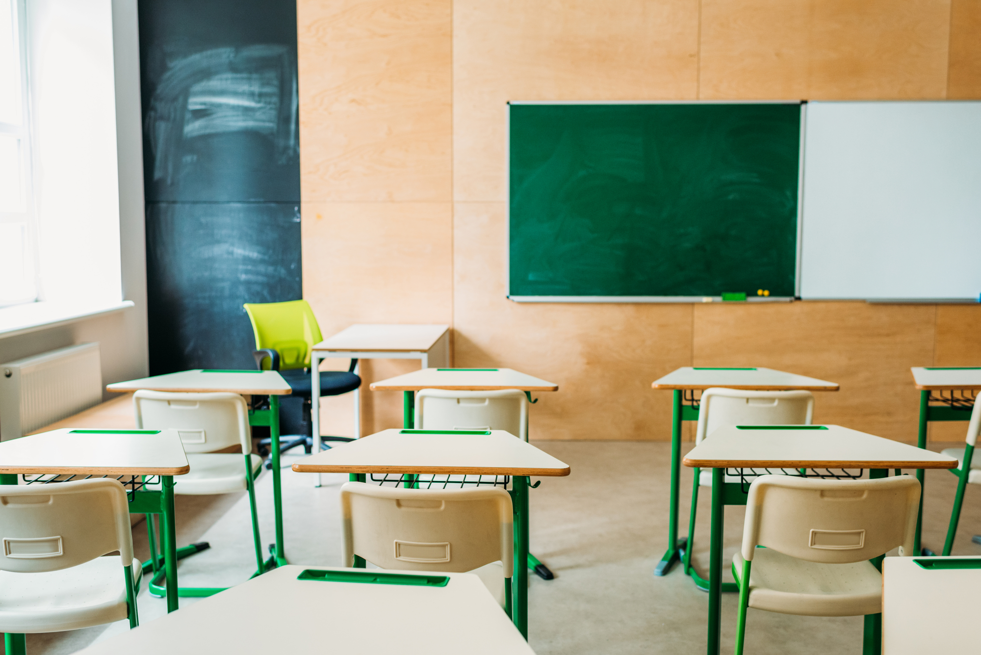 Interior of empty modern classroom with blank chalkboard at school