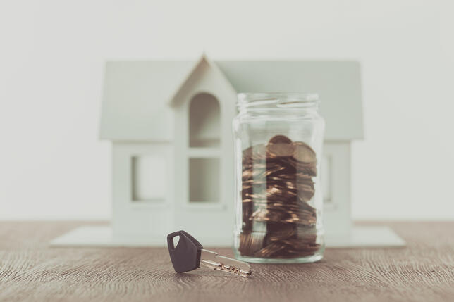 Key near jar of coins on table with small house on background, saving concept