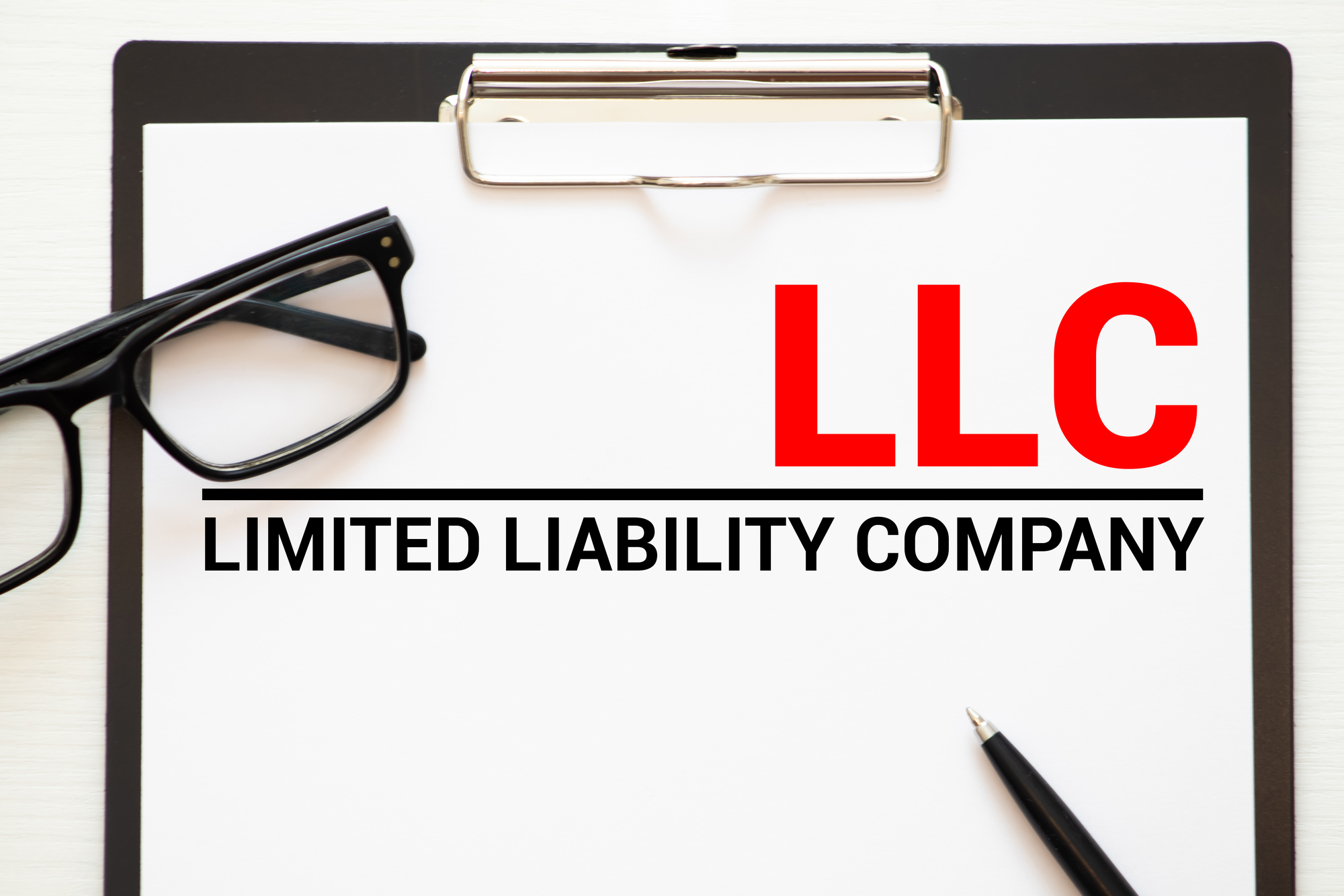 LLC Limited Liability Company - handwriting on paper with cup of coffee and pen, acronym business concept