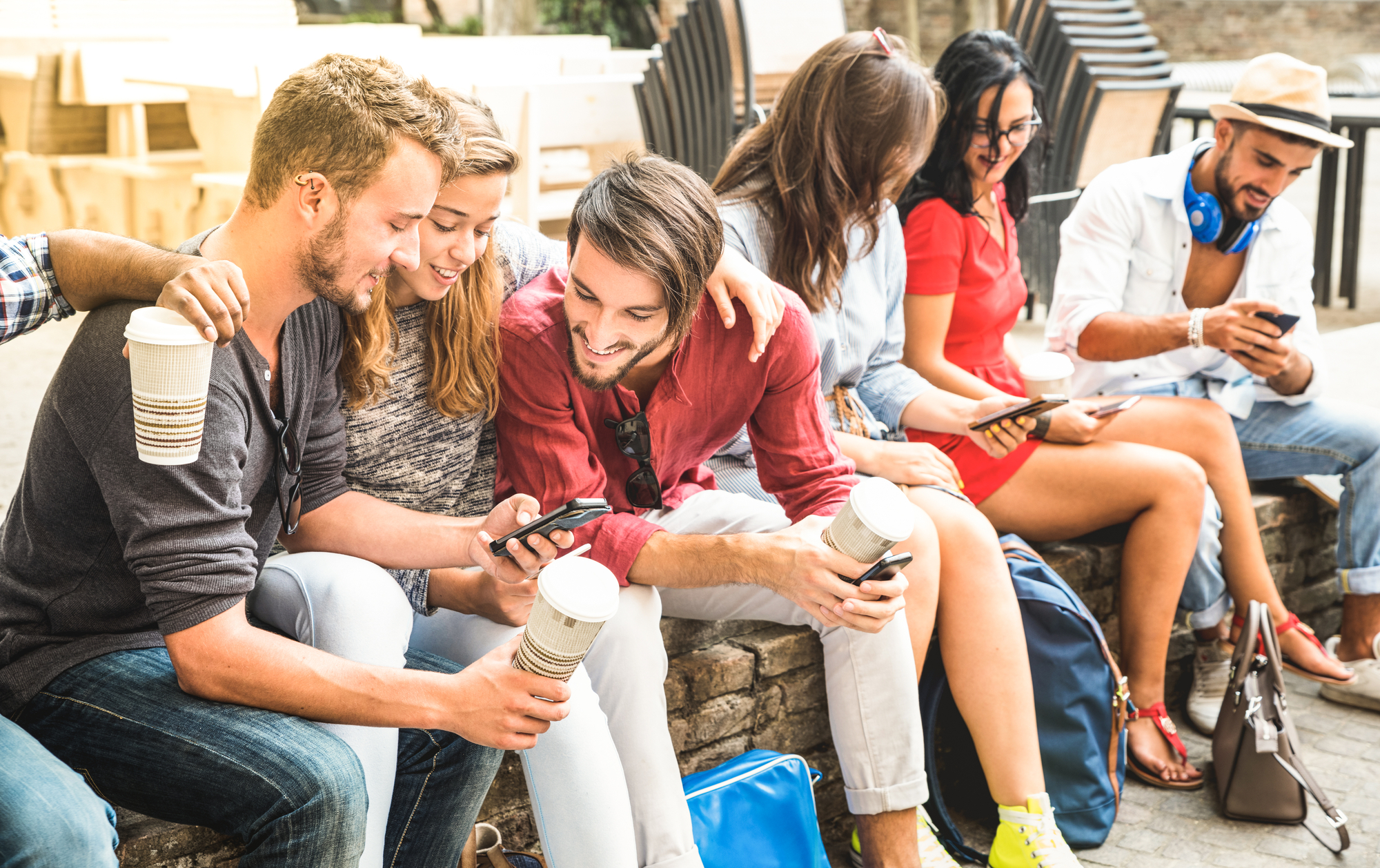Multiracial millennials group using smart phone at city college backyard - Young people addicted by mobile smartphone - Technology concept with connected trendy friends - Warm vibranc