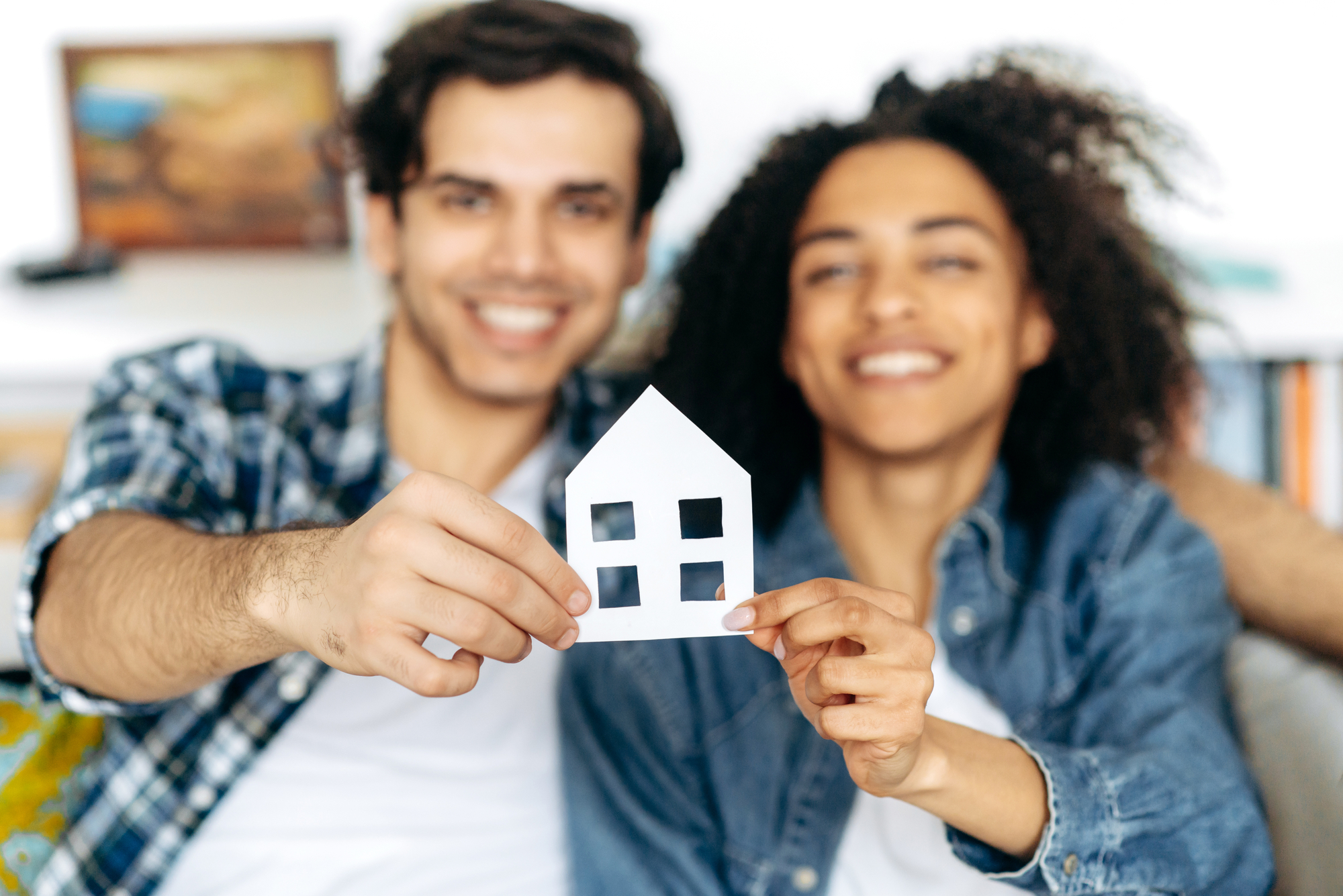 New home owners Joyful multiethnic couple holding paper house, sitting on a sofa in their new modern apartment or house