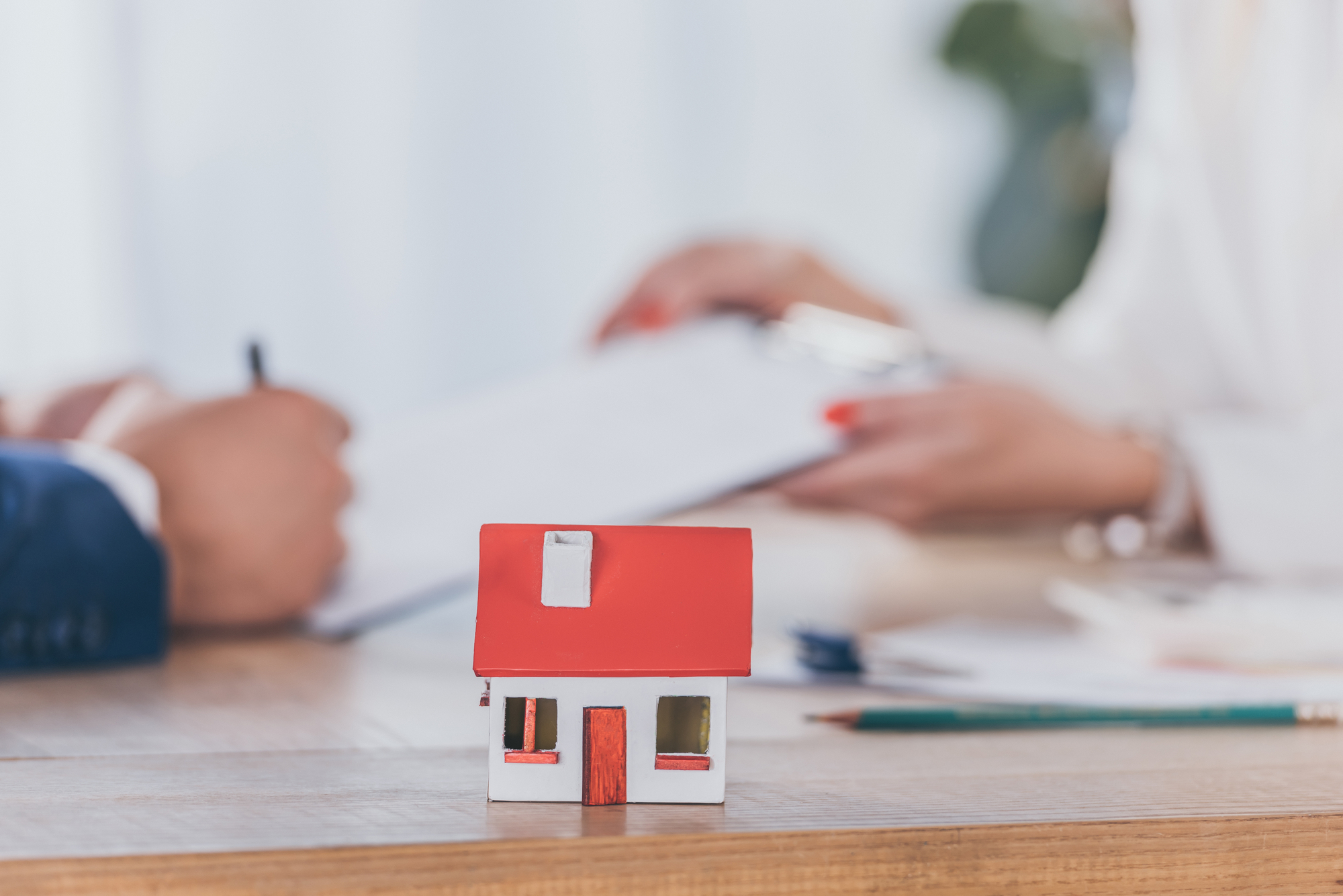 Selective focus of house model near businesswoman holding clipboard and client signing contract