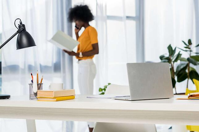 Selective focus of laptop at workplace and african american freelancer talking on smartphone on background at home (R) (S)