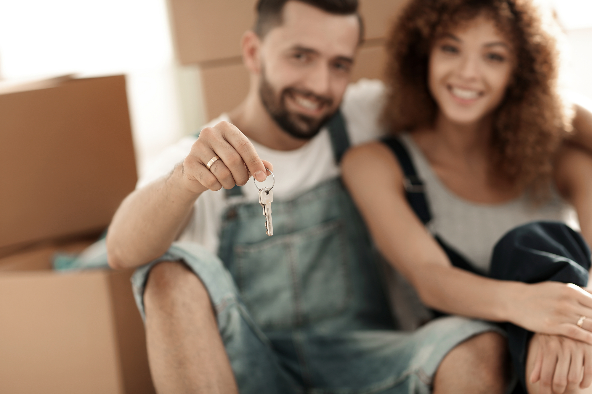 Smiling couple on the background of large cardboard boxes