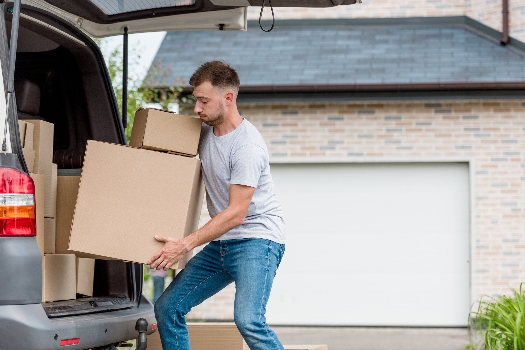 Strenuous young man moving boxes from car into new house