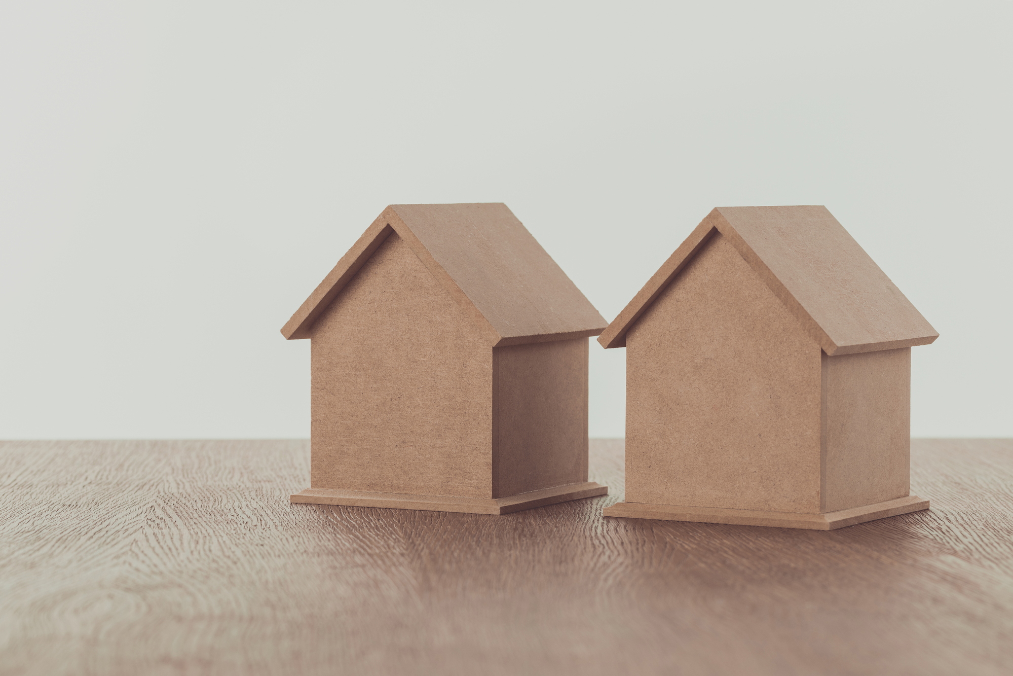 Two small wooden houses on wooden tabletop, saving concept