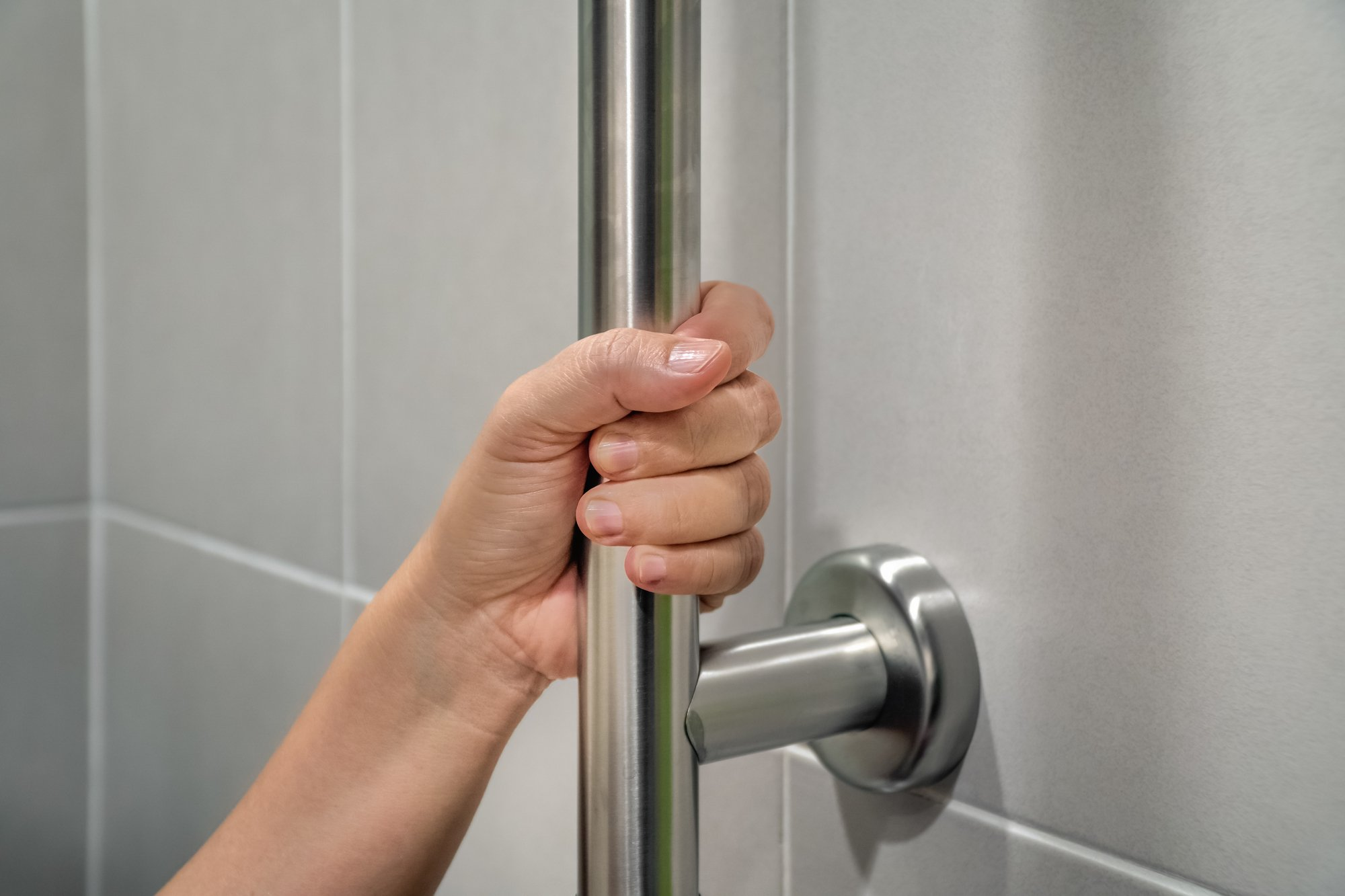 Woman holding on handrail in toilet