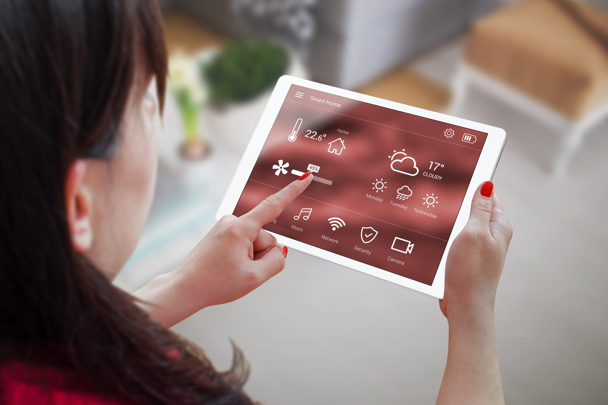 Woman use application for smart home control on tablet. Interior of living room in the background