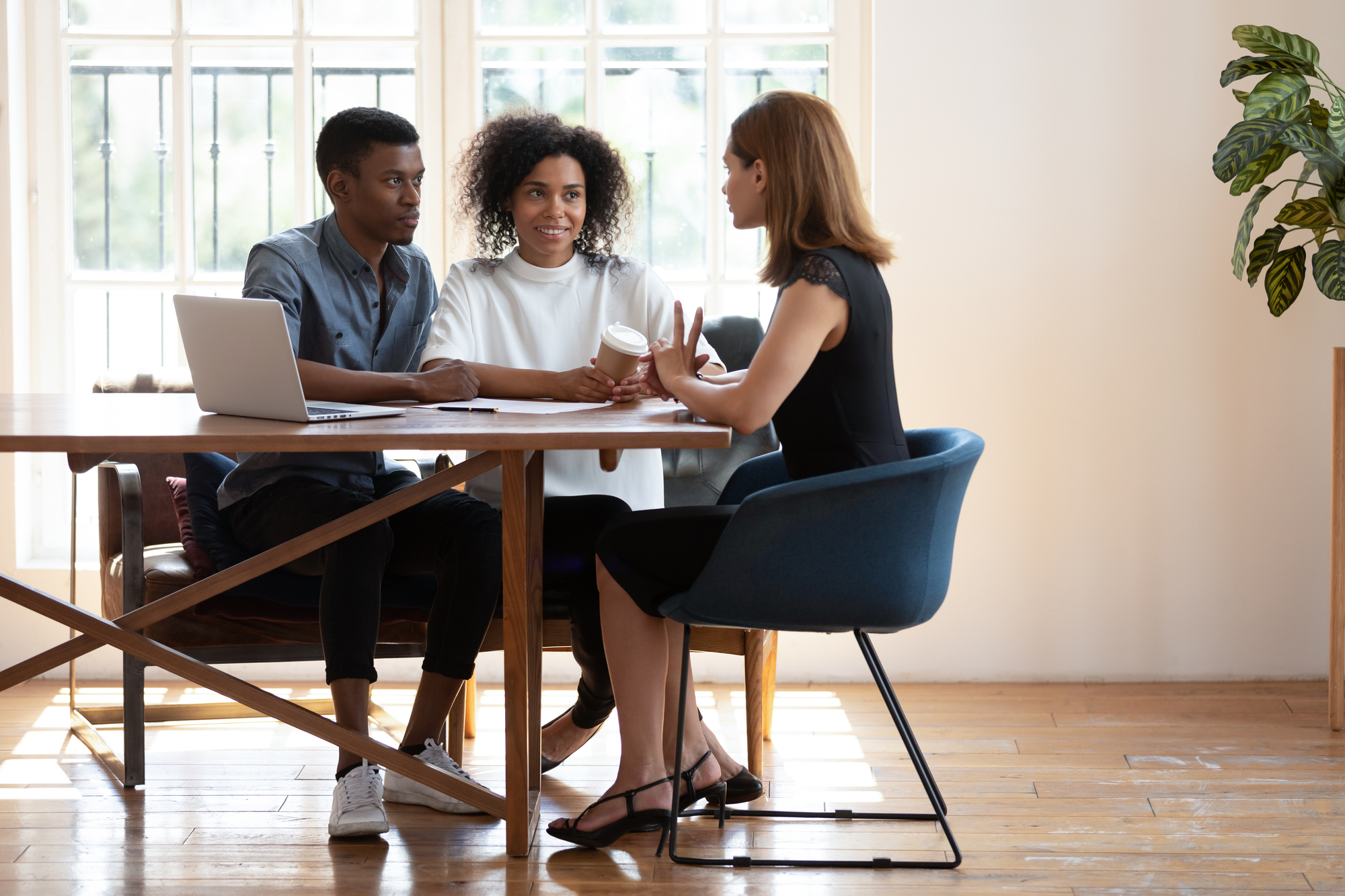 Young biracial couple consulting talking with female designer at meeting — Stock Image