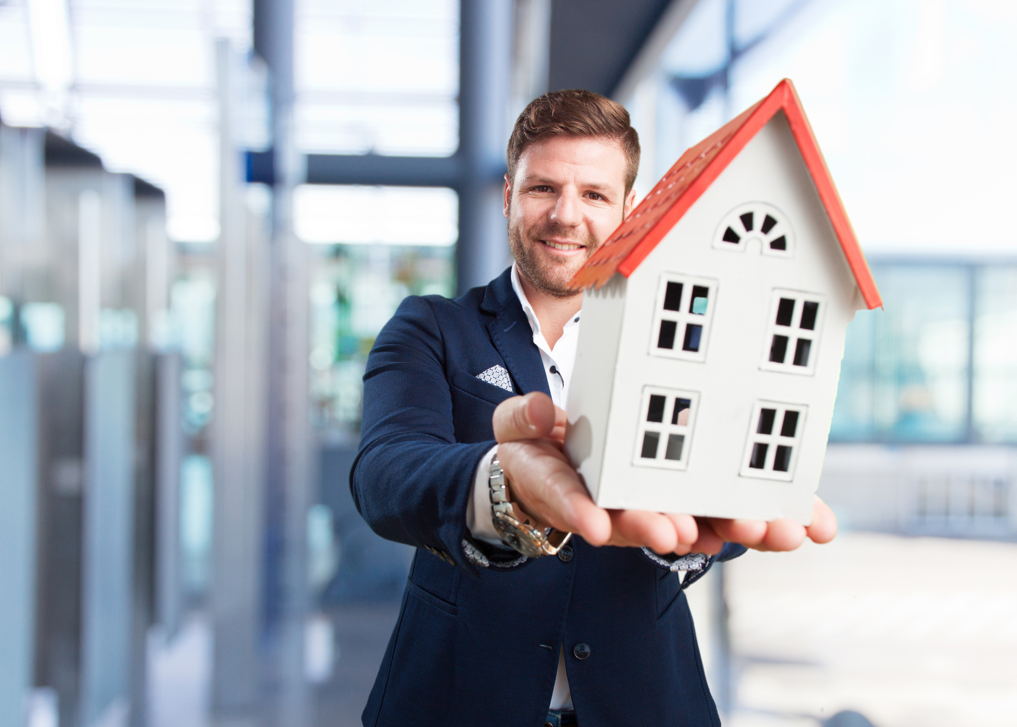 Young businessman with toy house