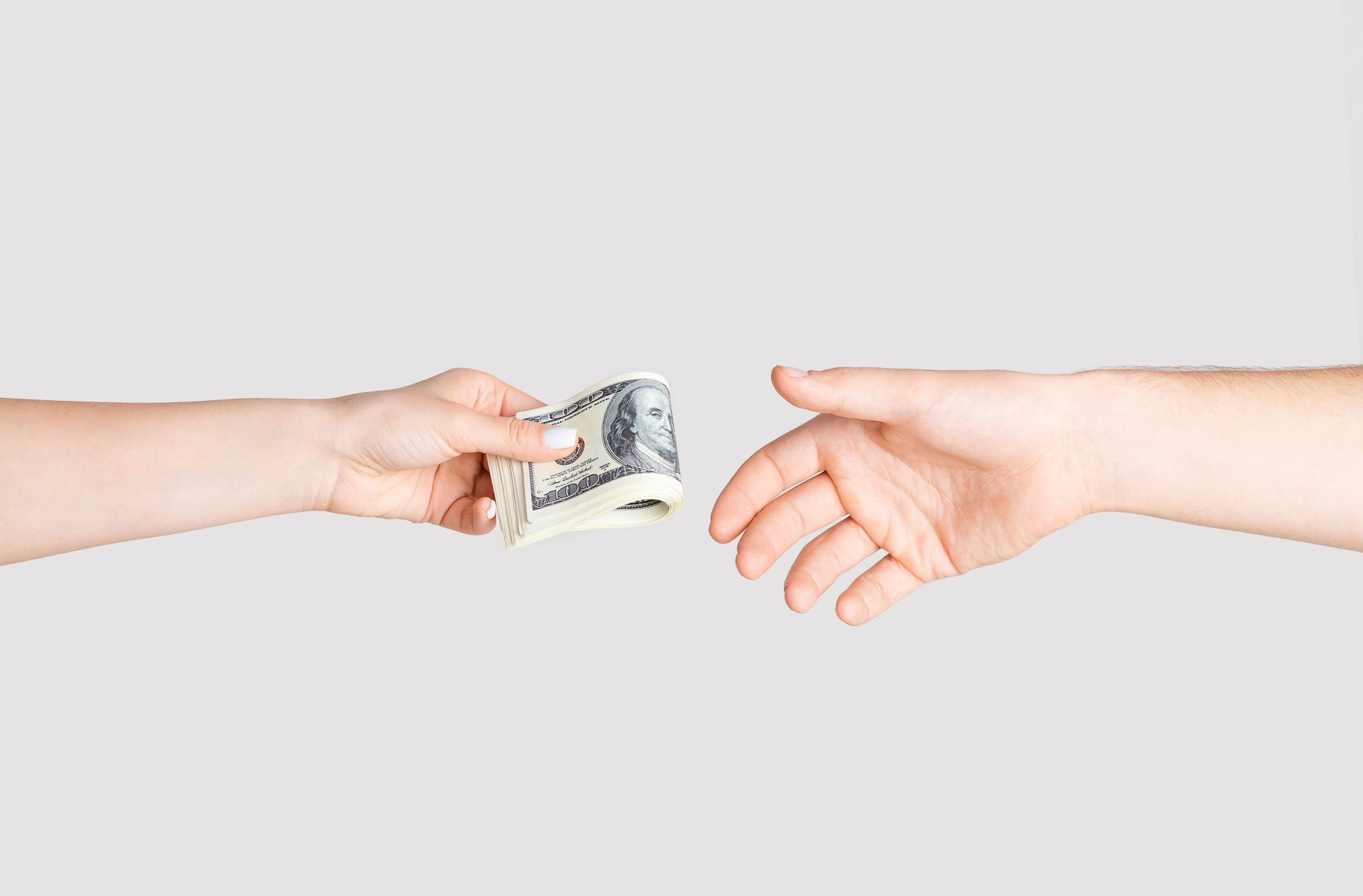 Young woman giving money to man over white background, close up of hands