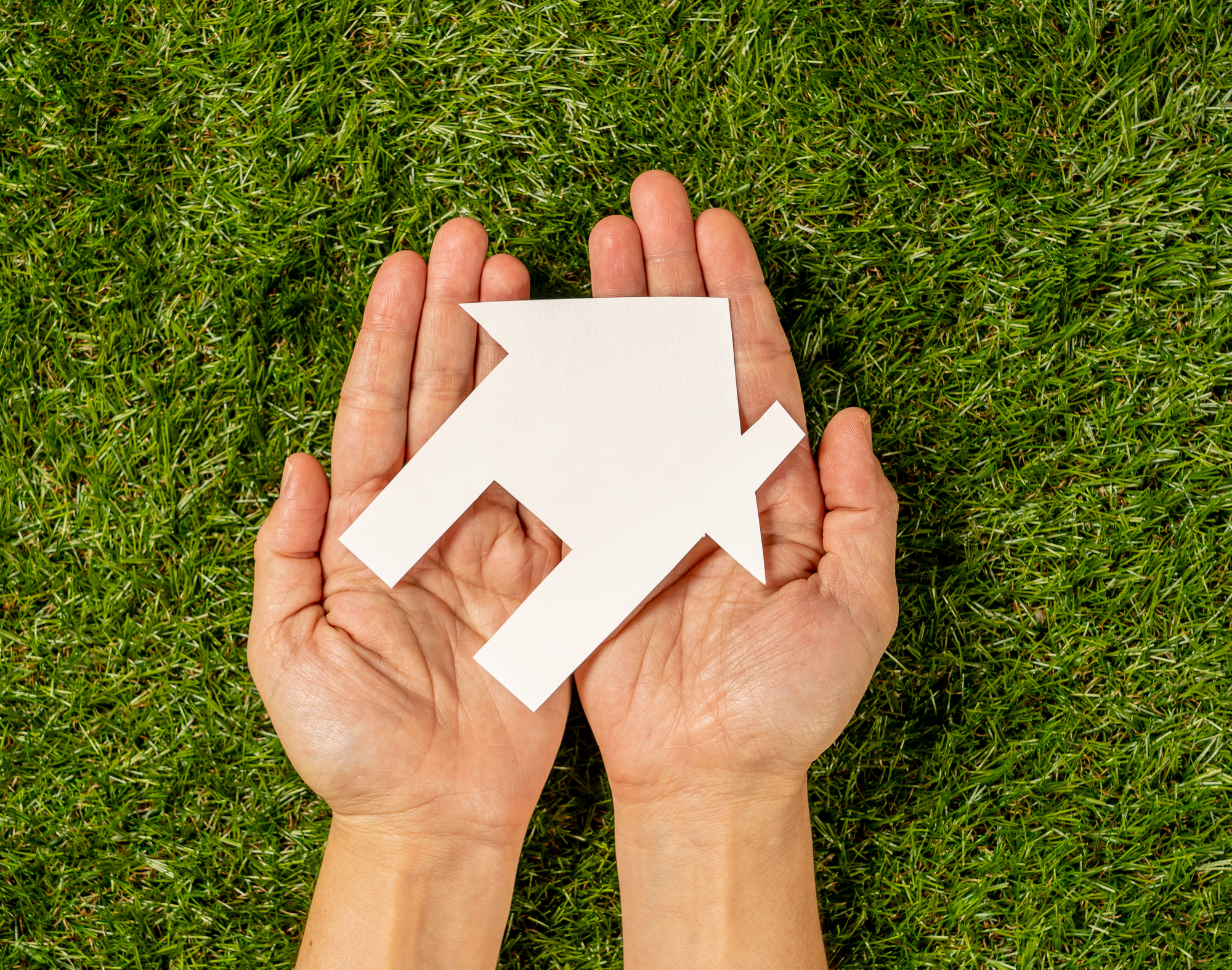 woman hands holding white house over green grass field in Property investment Real estate Saving and buying a home mortgage and loan banking